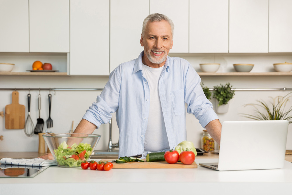 Picture of mature attractive man standing at the kitchen using laptop computer and cooking salad. Looking at camera.