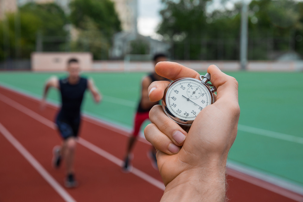 Picture of young athlete men run on running track outdoors. Historic stop watch time measurement.