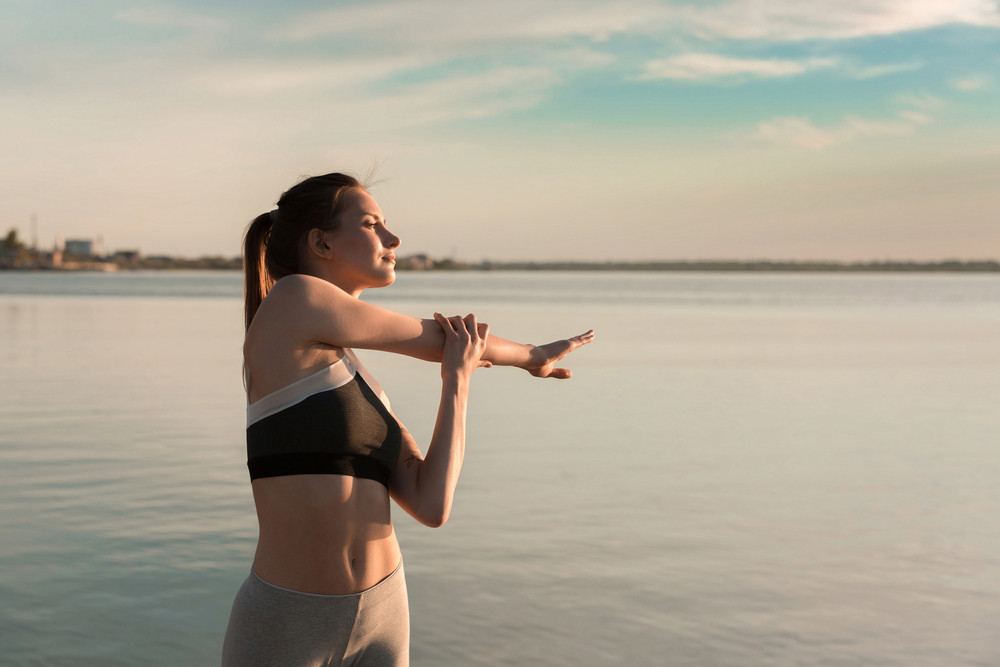 Picture of young sports woman at the beach make stretching exercises.