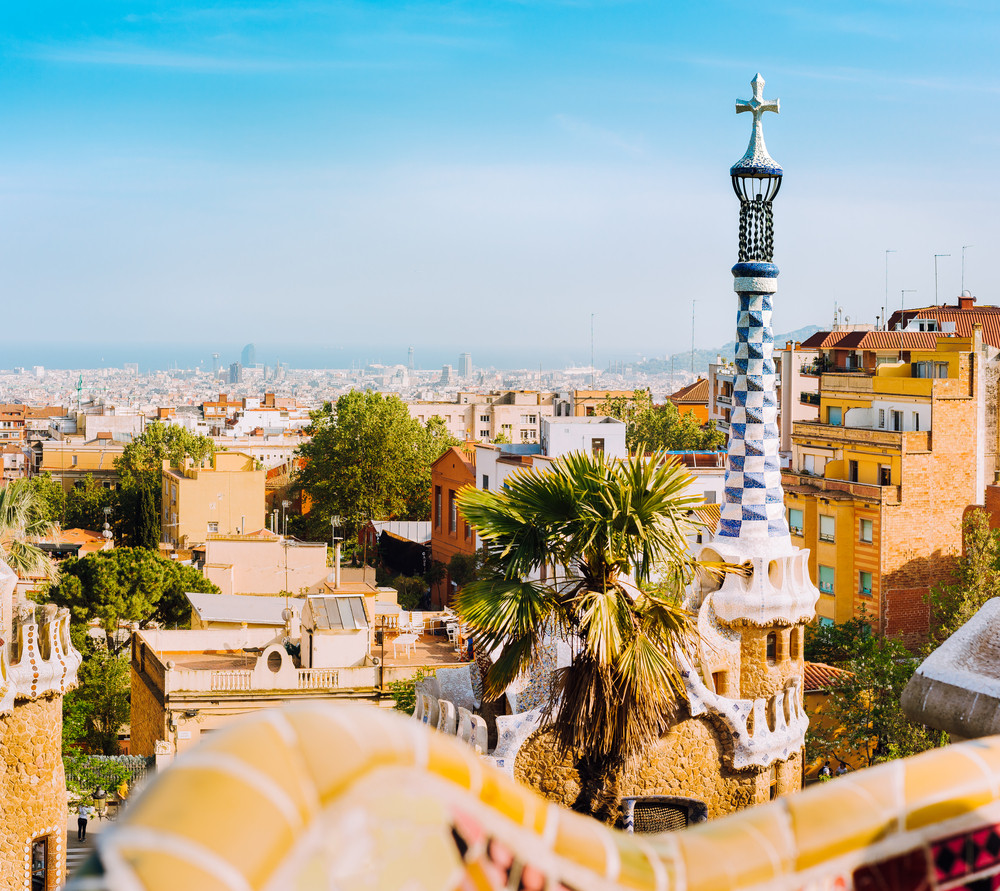 Porter lodge colorful tower and details of ceramic bench in Park Guell. Warm sunlight on rooftops. Barcelona, Catalonia, Spain Catalonia, Spain, Europe