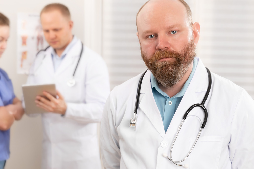 Portrait of a confident real doctor standing in front of his health team