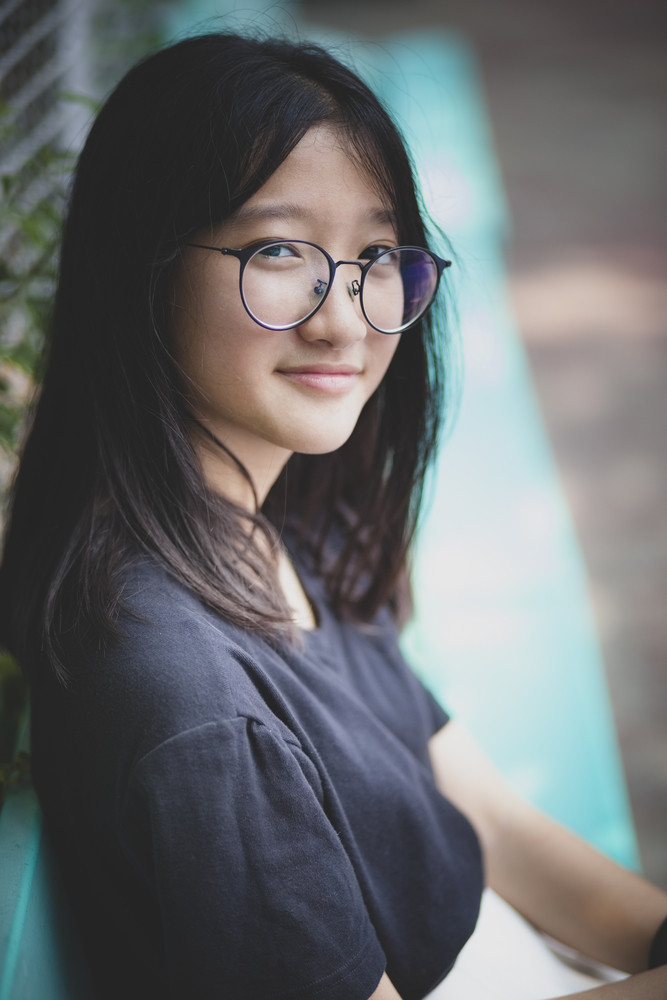 portrait of asian teenager looking with eye contact to camera