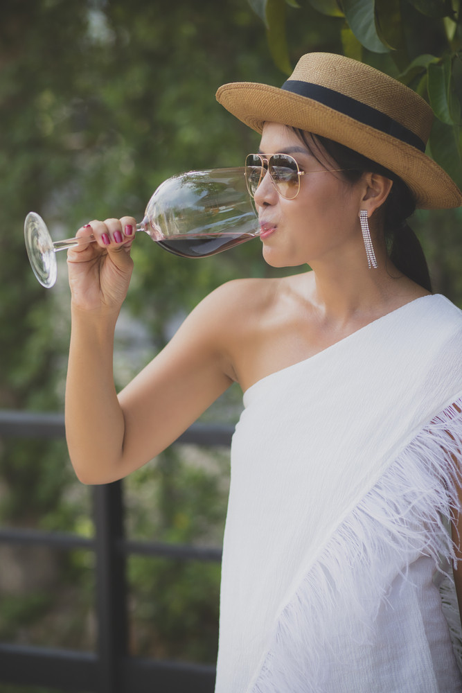 portrait of beautiful asian younger woman drinking red wine in elegance wineglass