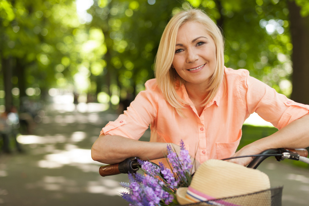 Portrait of beautiful woman with bike in summer day