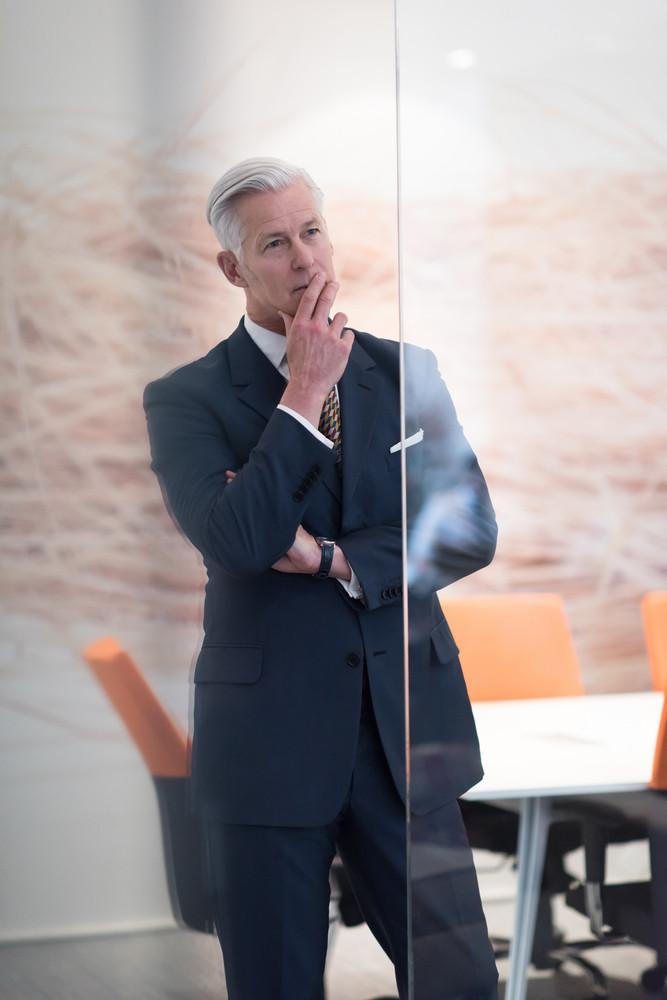 portrait of handsome senior business man at modern office meeting room interior