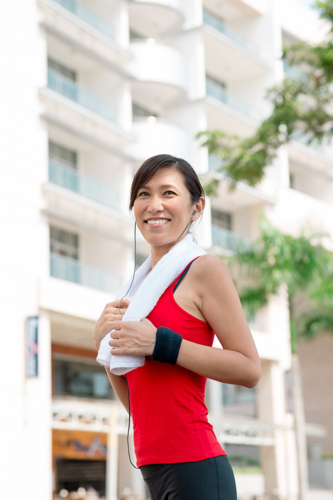 Portrait of happy female runner with a towel