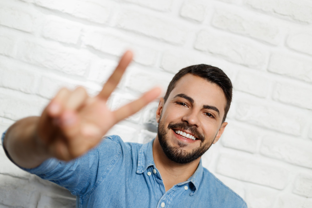 portrait of happy man smiling italian guy winking at camera and
