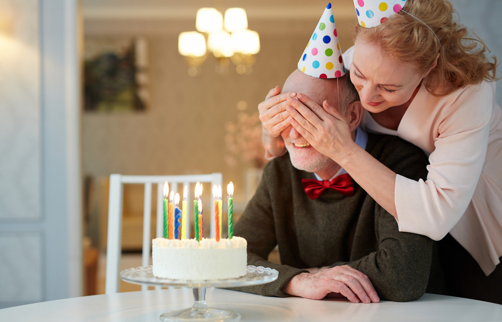 Portrait of loving senior couple celebrating birthday together, mature woman closing eyes of smiling old man presenting him birthday cake with candles as surprise