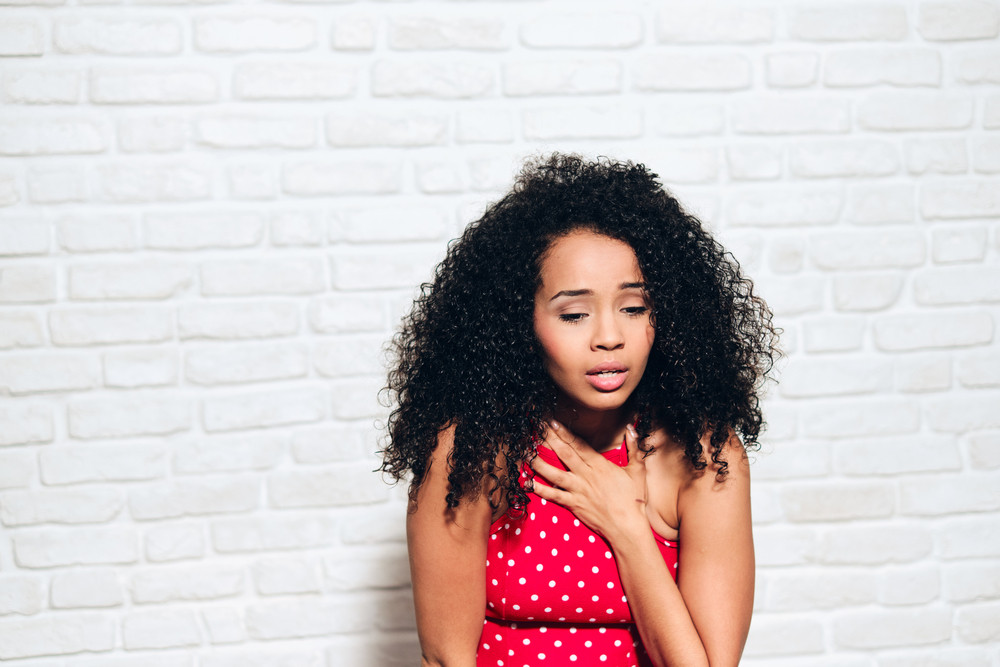 Portrait of nervous african american woman with panic attack. Black girl showing anxiety, sadness and frustration. Sad hispanic person against white wall