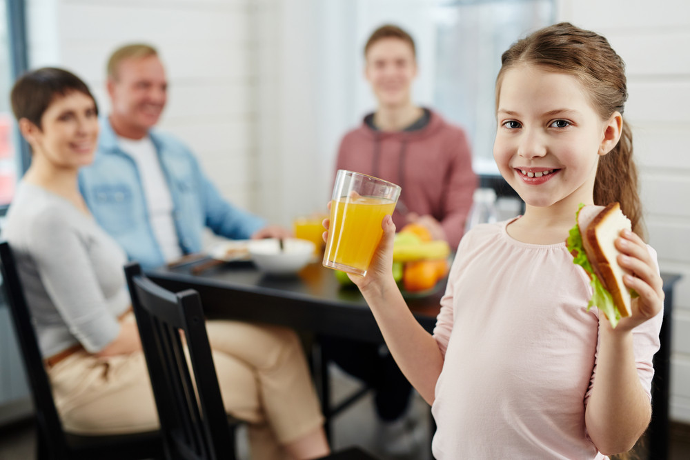 Portrait of primary age girl posing for photography with glass of orange juice and healthy sandwich, her family looking at her while sitting at dining table