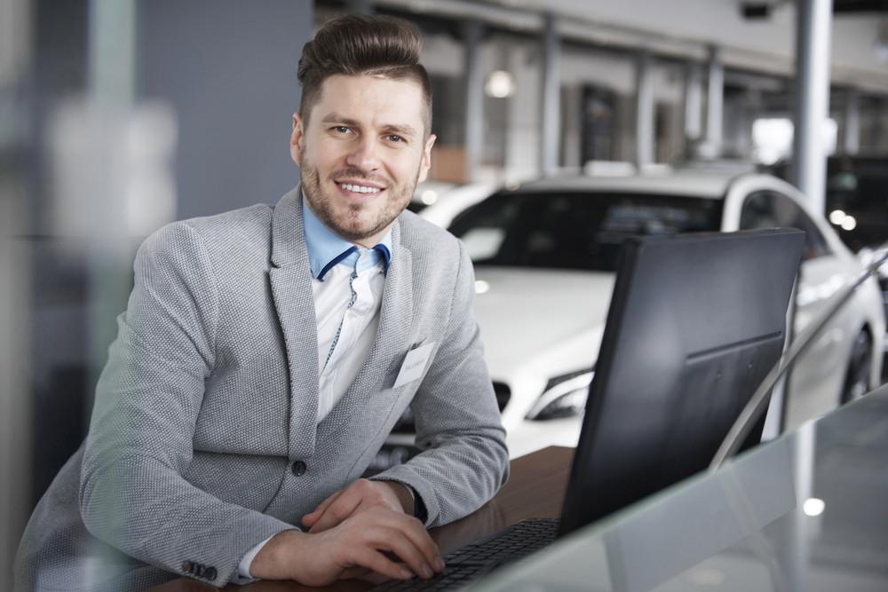 Portrait of salesman leaning at computer desk