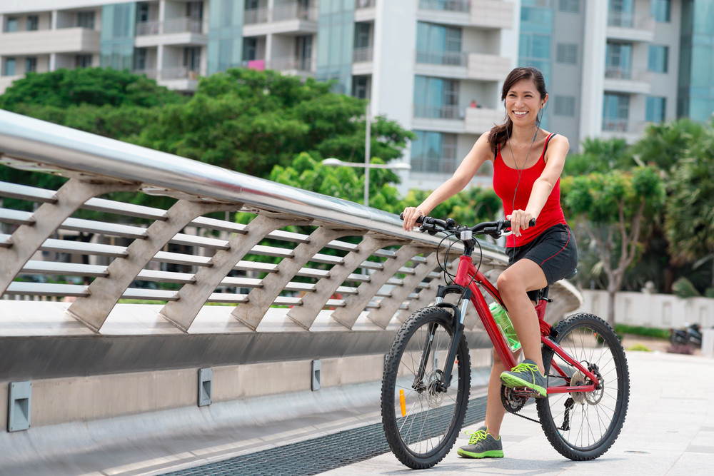 Portrait of smiling Asian woman listening to the music and riding on bike