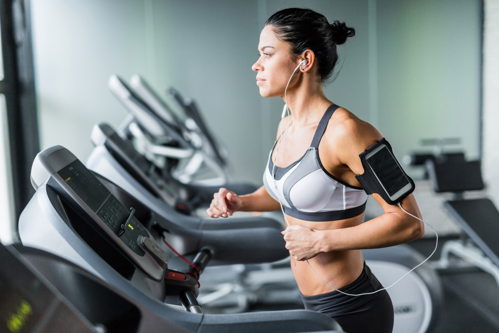 Portrait of sportive brunette woman exercising on treadmill in gym listening to music using shoulder smartphone holder