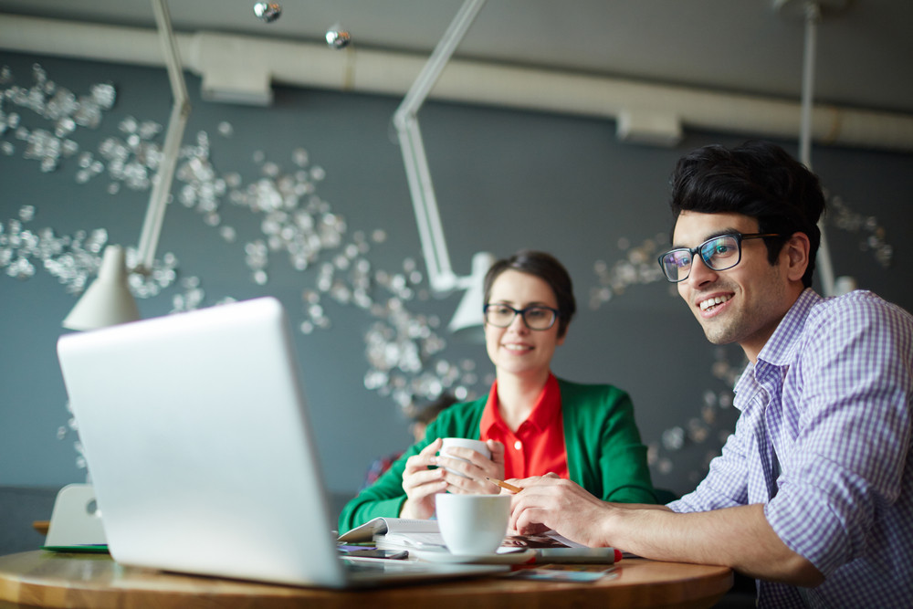 Portrait of two young creative colleagues man and woman both wearing casual clothes and glasses, working at meeting in cafe, smiling and looking at laptop screen