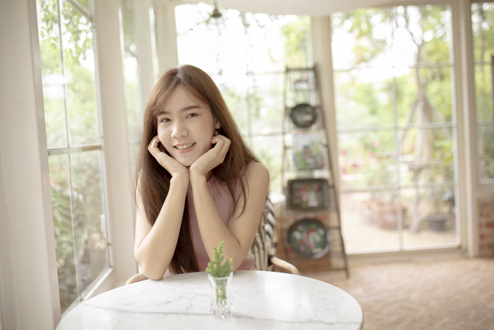 portriat of younger asian woman toothy smiling face with happiness emotion sitting in living room