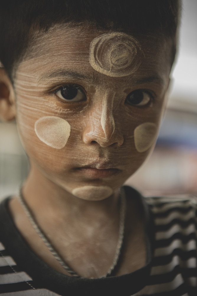 prachuap khiri khan thailand - september14,2018 : close up face of unidentified myanmar children with tanaka dressing on face looking to camera with eye contact