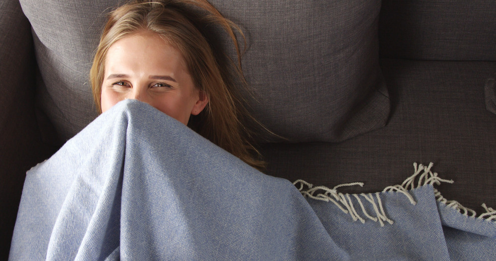 Pretty female model playing peekaboo with a light blue thin blanket lying on a dark grey couch