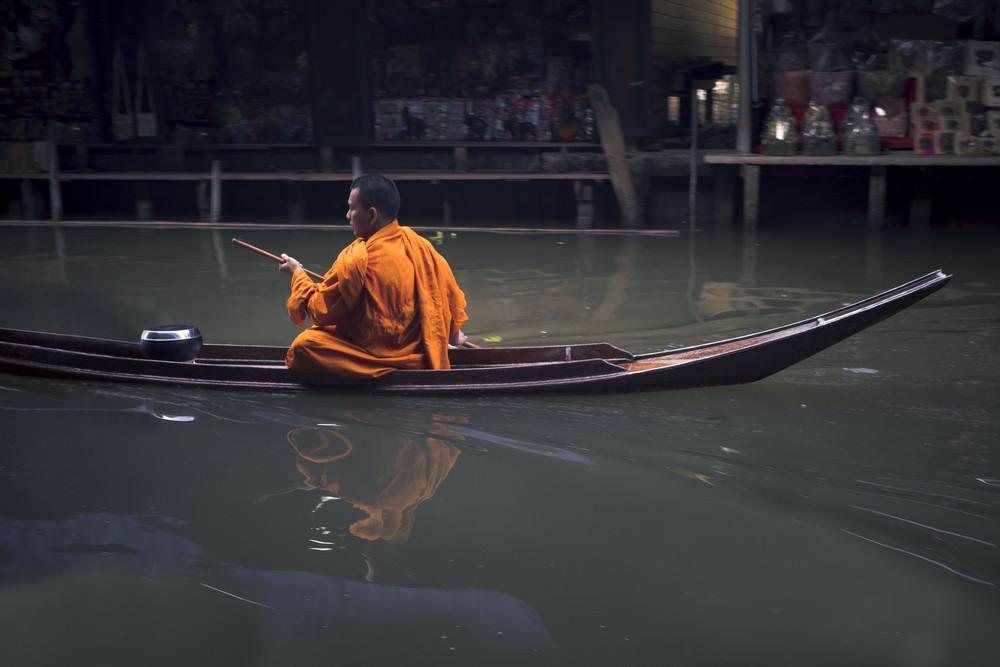 ratchaburi thailand - january1,2019 : thai monk sailing boat in dumneonsaduak canal ,floating market one of most popular traveling destination in ratchaburi thailand