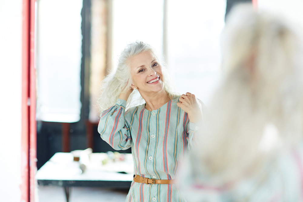 Retired woman looking at herself in mirror