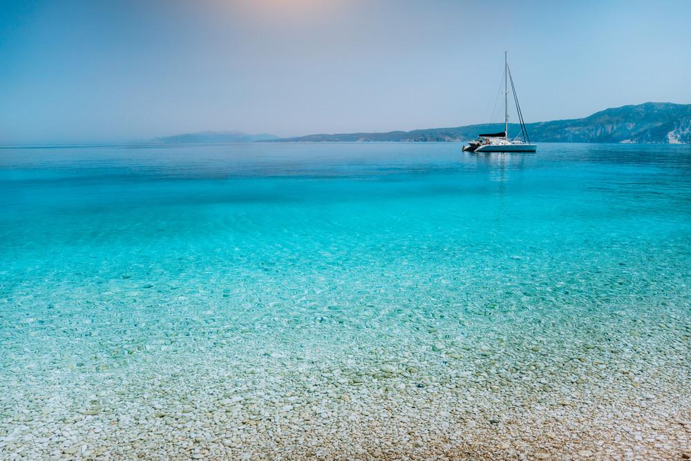 Sailing catamaran yacht boat at anchor near pebble beach with calm pure clear azure blue water surface