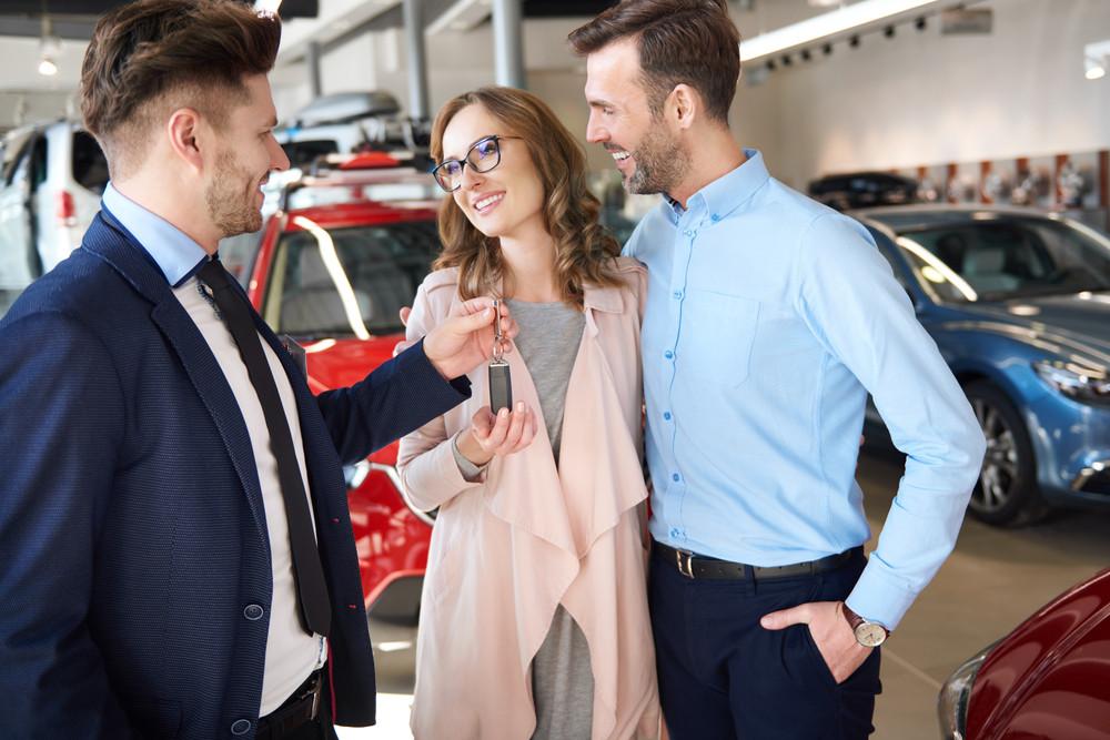 Salesman handing couple brand new car keys