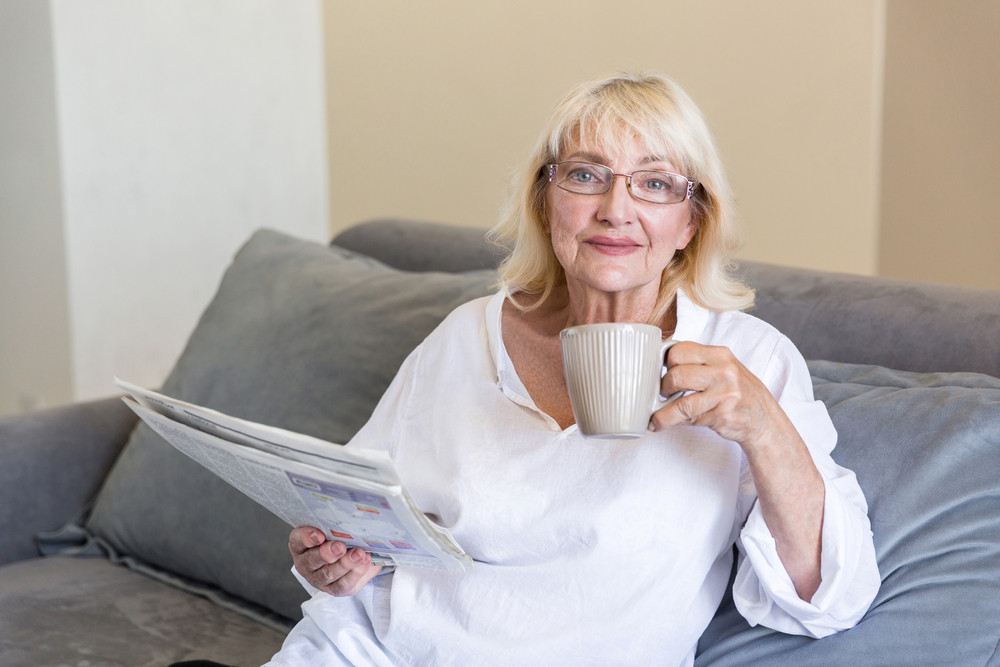 Senior woman in eyeglasses holding a newspaper while having a cup of coffee in the morning on a couch a home