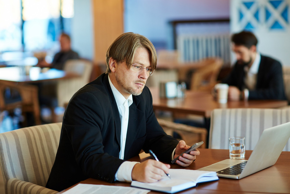 Serious businessman with smartphone making notes in notebook and looking at laptop display