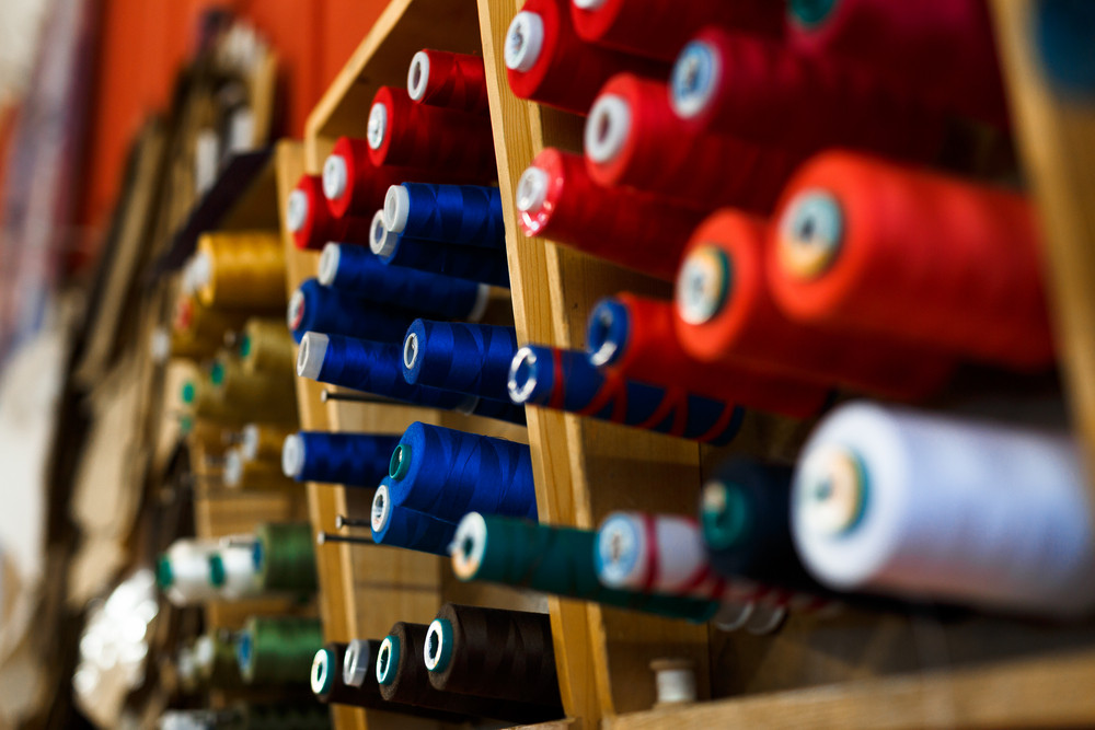 Set of multi-colored spools in workshop of tailor
