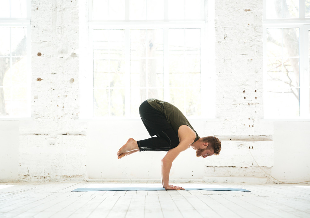 Side view of a man practicing advanced yoga indoors