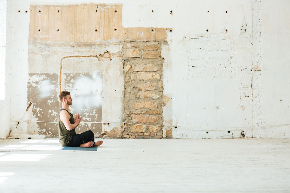 Side view of a man sitting on a fitness mat and meditating in the gym