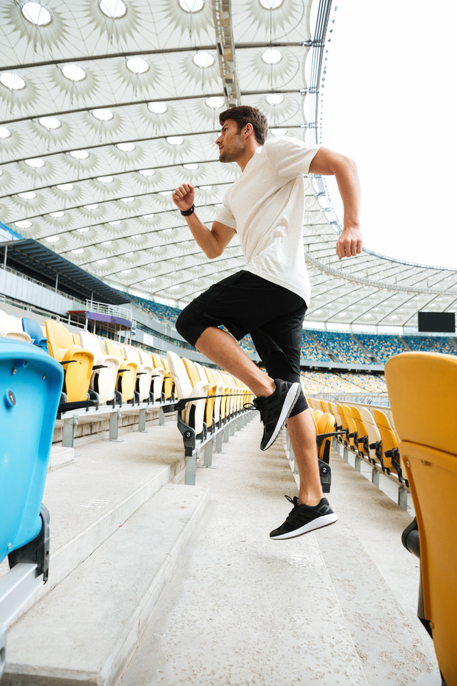 Side view of a sporty athlete man running upstairs at the stadium