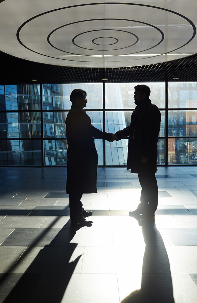 Silhouettes of two business partners shaking hands while standing in spacious office lobby with panoramic windows, profile view