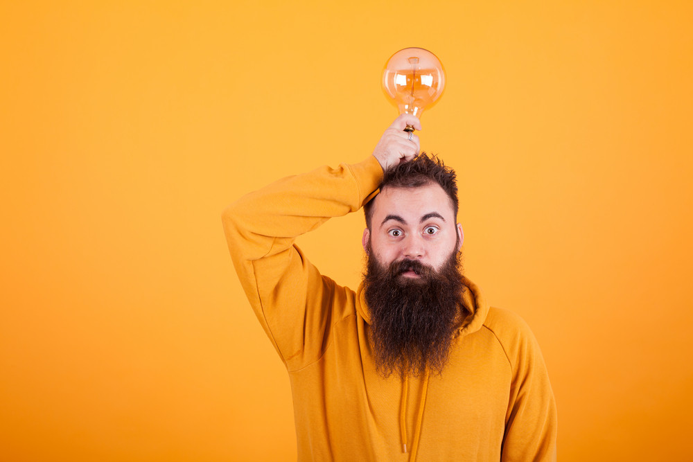 Smart bearded man holding light bulb on his head over yellow background. Creative mind. Bright idea. Succesful man.