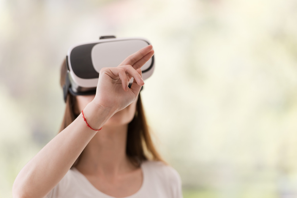 65a5257929dd Smile happy woman getting experience using VR-headset glasses of virtual  reality at home