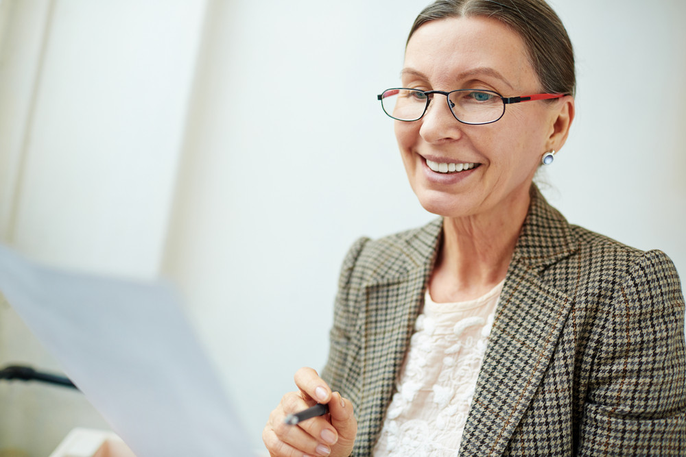 Smiley woman in eyeglasses reading business document