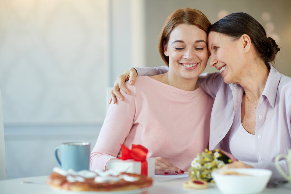 Smiley young woman and her mother celebrating mother day at home