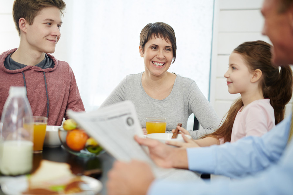 Smiley young woman talking to her husband by breakfast