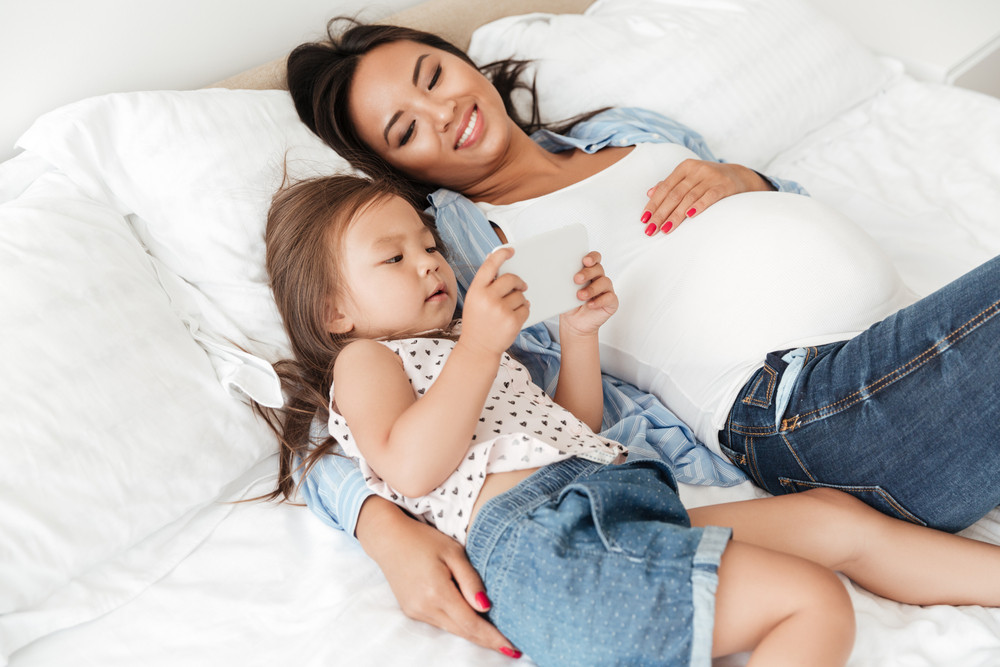 Smiling young pregnant woman and her little daughter using mobile phone while lying together in bed at home