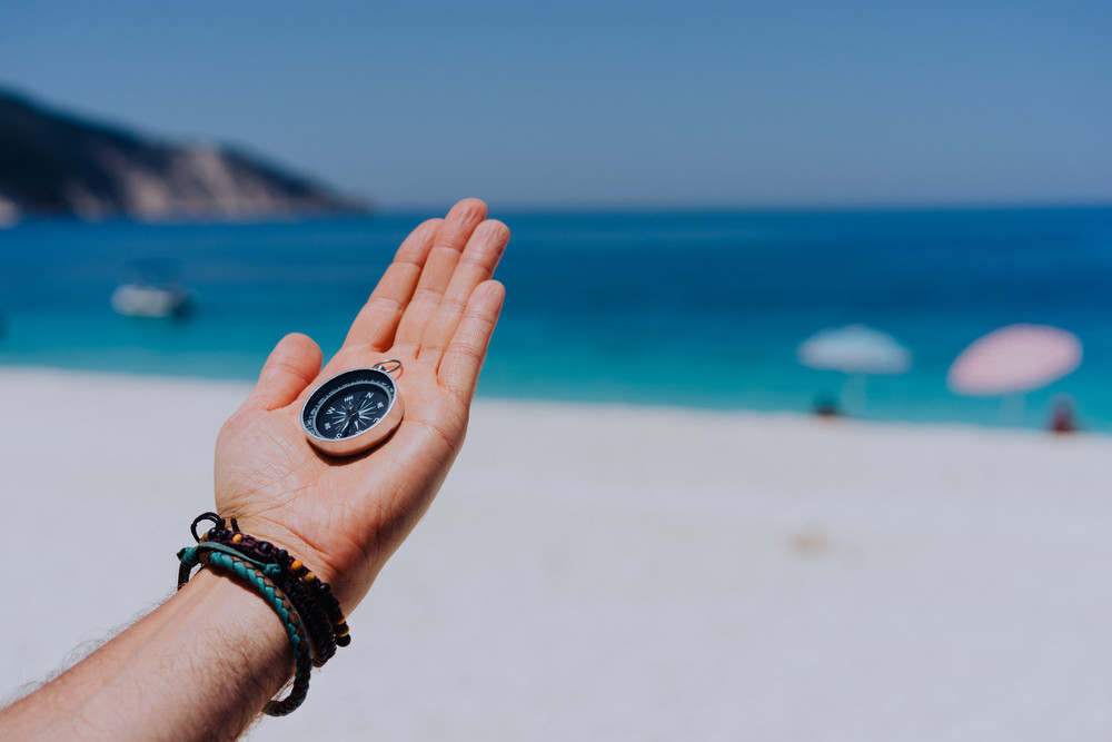 Stretched hand palm with black metal compass against sandy beach and blue sea. Follow your way, goal, wish concept. Point of view pov