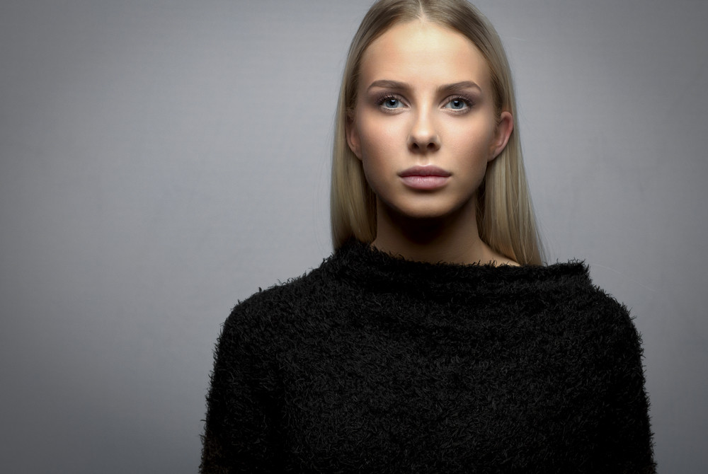 Studio portrait of a young blonde woman with fury jacket