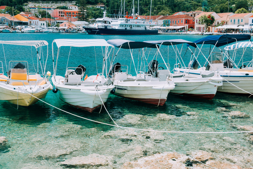 Summer scenery of port Fiskardo. Small day trip boats tied up to the pier. Picturesque outdoor scene of Kefalonia island, Greece, Europe. Traveling vacation concept