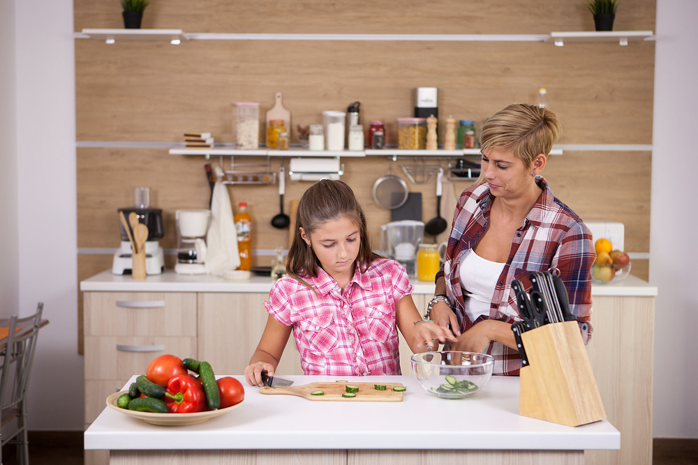 Teenage girl and her mother making healthy food for dinner. Happy family.