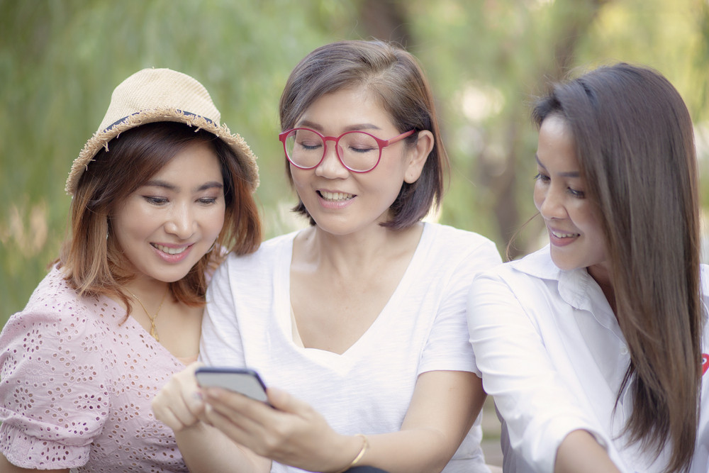 three asian woman looking on mobile phone screen with toothy smiling face