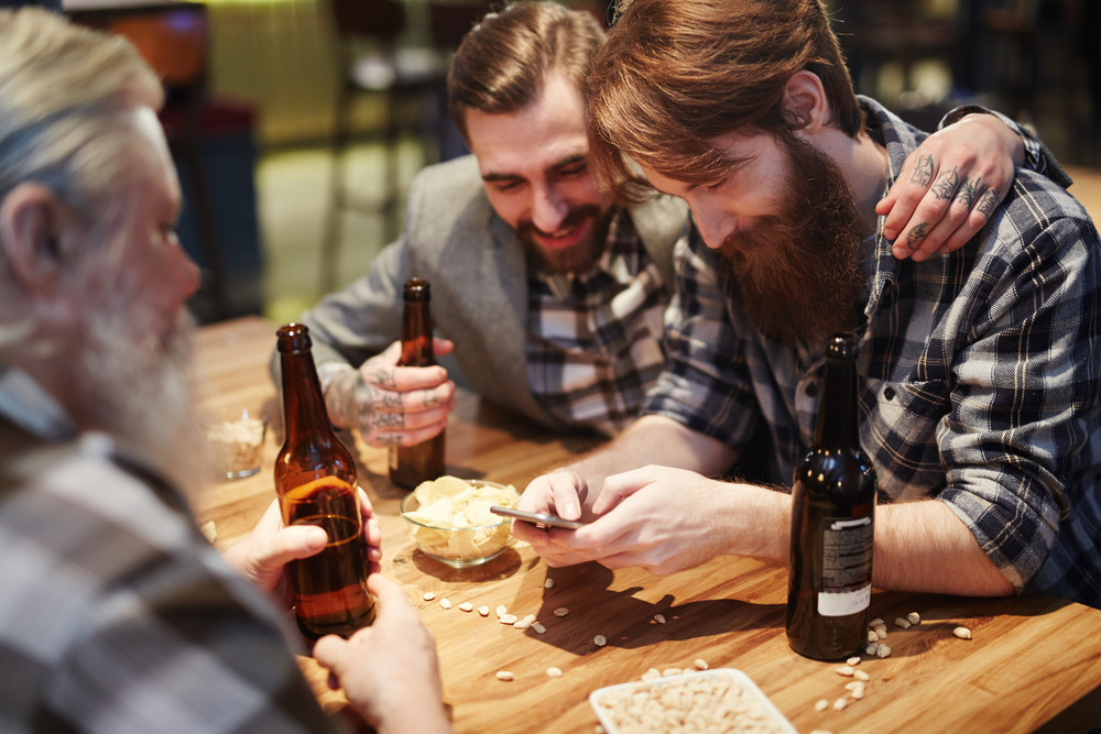 Three bearded men with bottles of beer spending time in pub