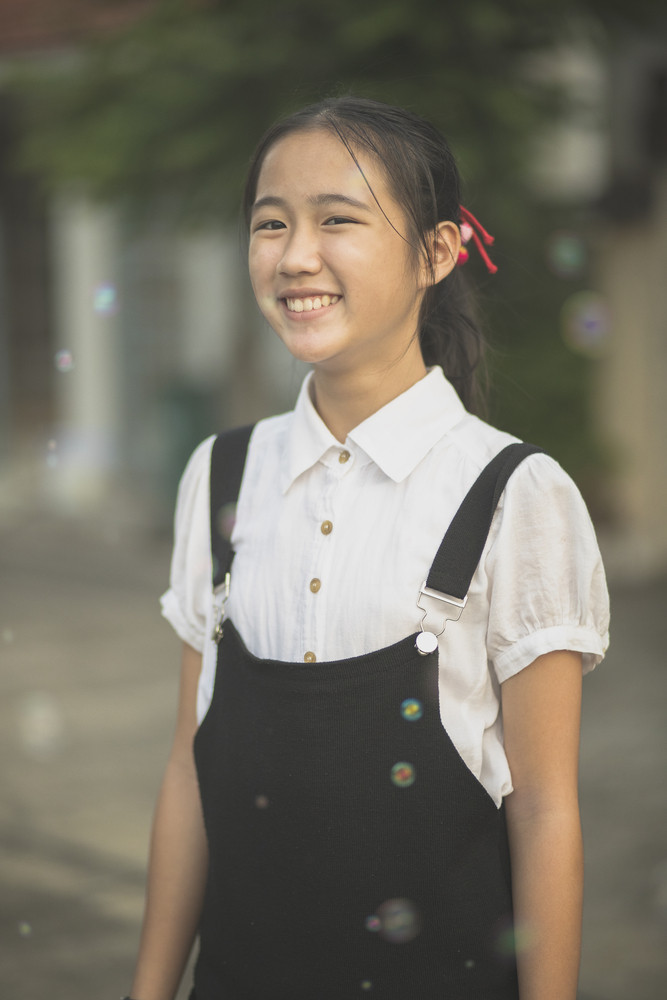 toothy smiling face of asian teenager wearing white and black suit standing outdoor
