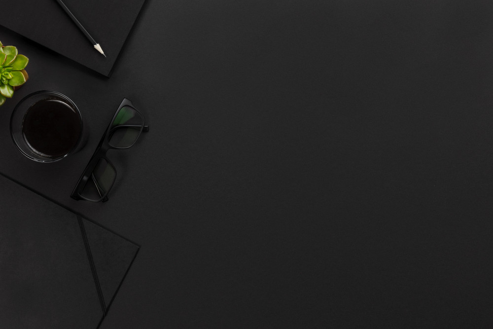 Top view of black office desk with notebook and supplies