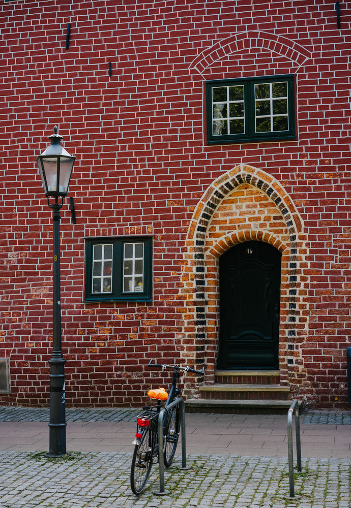 Traditional medieval german brick house in Luneburg, Germany. Fragment sticking out of the facade. Bicycle parked