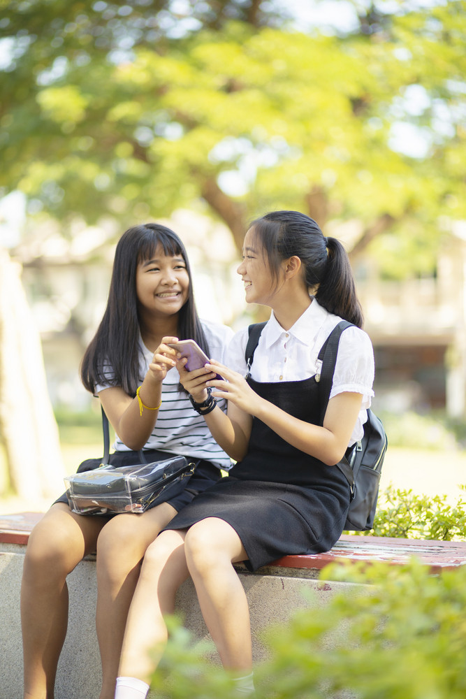 two asian teenager happiness face holding smartphone in hand talking wiht relaxing  emotion