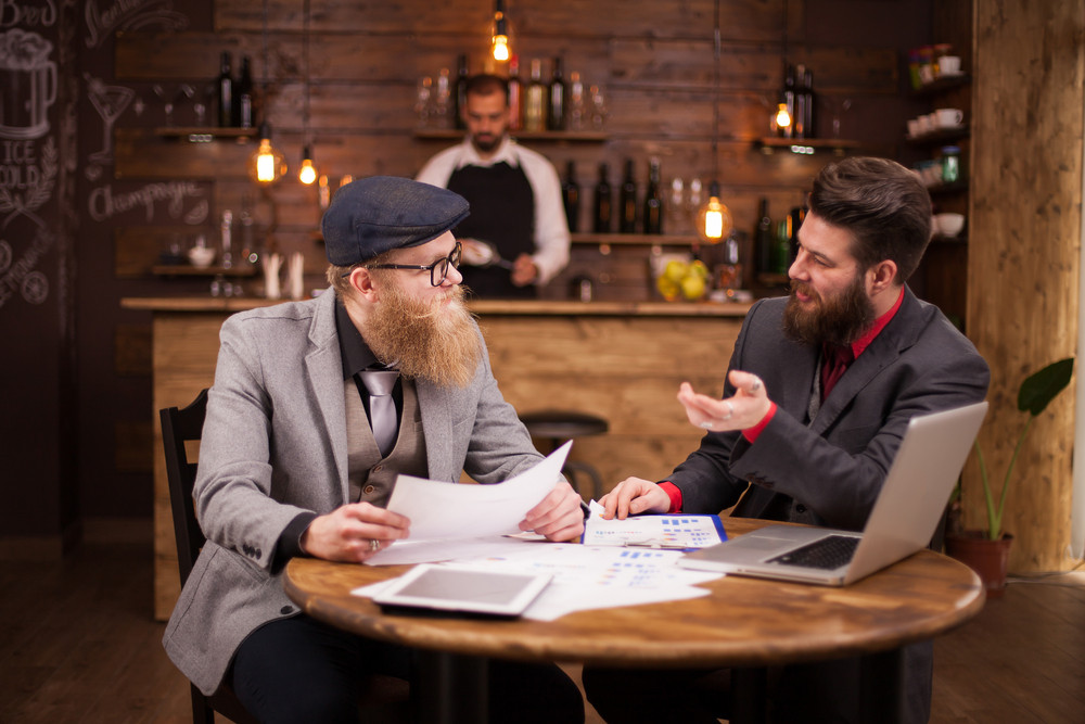 Two bearded economists having a business meeting in a coffee shop. Caucasian men. Handsome men. Good team work.