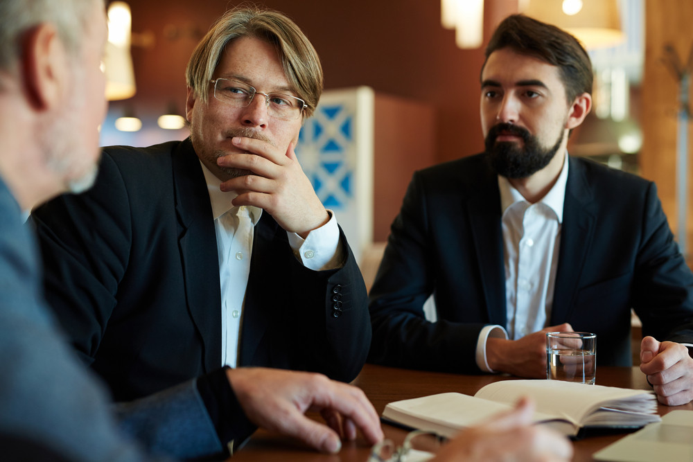Two white collar workers listening to their coworker with concentration while he sharing ideas concerning new promising project, waist-up portrait